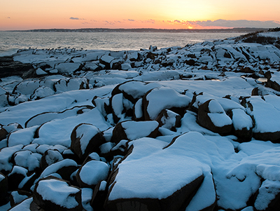 Snow covered rocks along the rocky Maine coast.