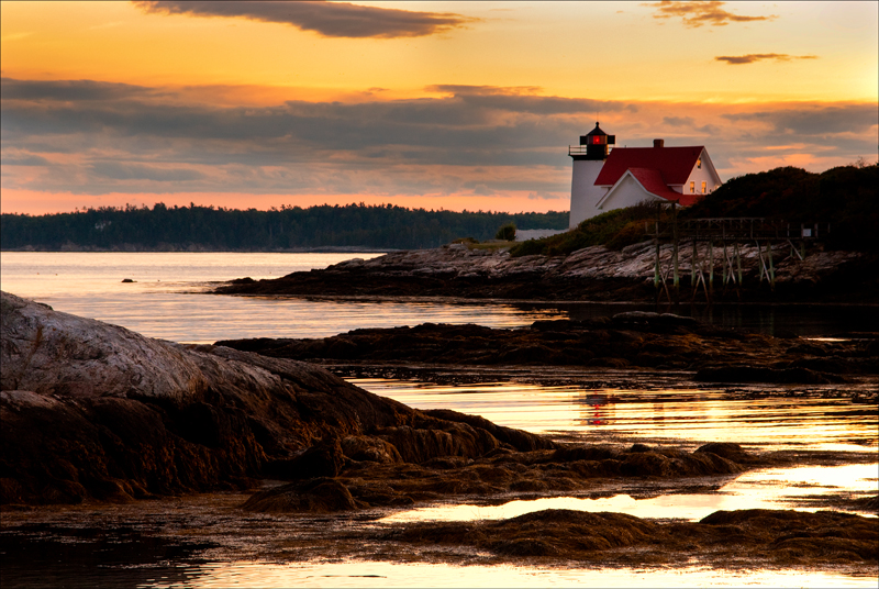 Sun setting by Hendricks Head light near Boothbay Harbor in Maine.