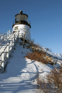 Historic Owl's Head Lighthouse sits on a snow covered cliff in Maine.