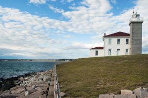 Watch Hill Lighthouse along rocky shoreline in Rhode Island.