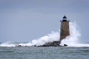 Huge waves crash around Whaleback lighthouse after storm tidal surge in Maine. Waves created by astronomically high tides after storm passes out in the ocean.