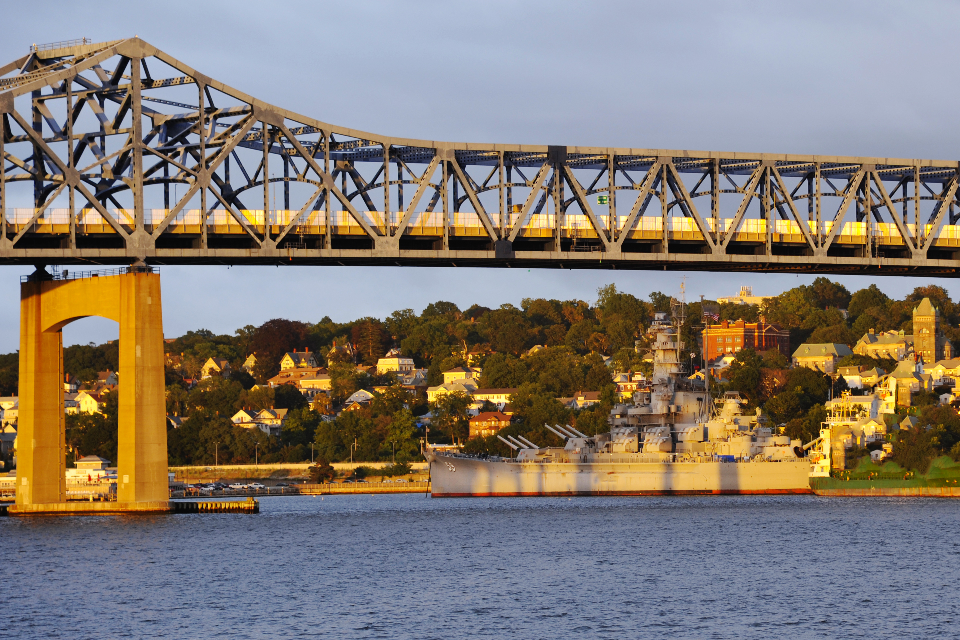 Setting Sun Illuminates Battleship Under Bridge