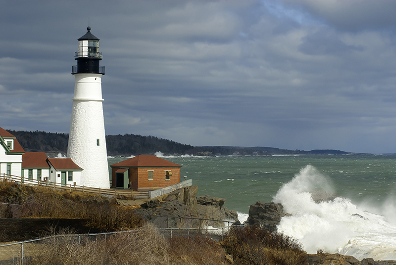 Sunlight Breaks Through Clouds on Portland Lighthouse with Huge Waves