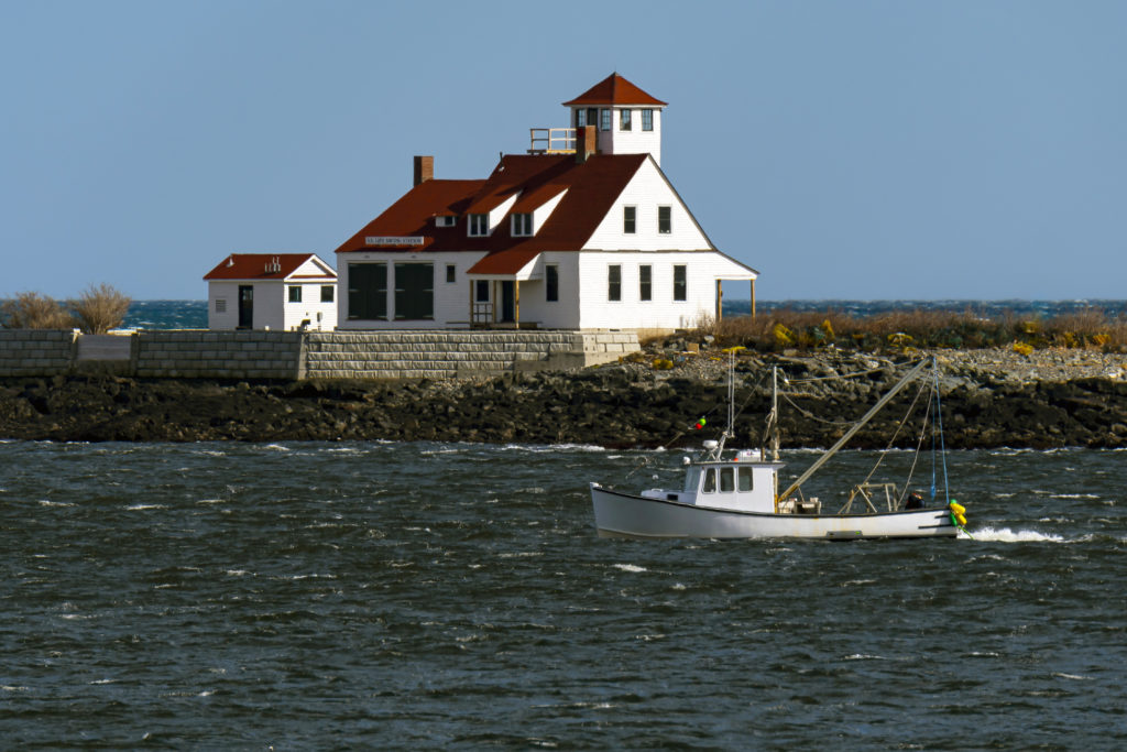 Lobster boat passes by the Wood Island Lifesaving Station, also referred to as Jerry's Point Lifesaving Station, under restoration, on Wood Island, in southern Maine, during rough seas. Lifesaving stations coordinated with lighthouse keepers to aid in offshore rescues.